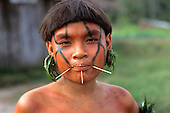 Roraima, Brazil. Young Yanomami woman with stick decorations through pierced cheeks and lips and aromatic leaf ear decorations.