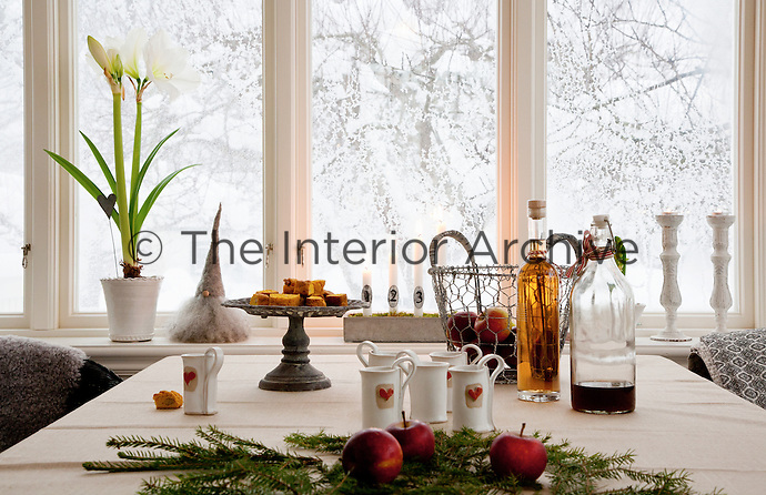A table laid for a warming Christmas coffee in the dining room, set against the wintery backdrop of a snowy garden
