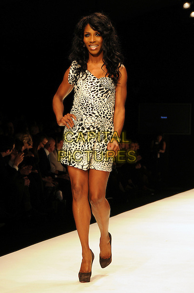 SINITTA (Sinitta Renet Malone).The Fashion For Relief Haiti 2010 show for London Fashion Week Autumn/Winter 2010 at Somerset House, London, England..February 18th, 2010.LFW catwalk runway full length black white leopard print dress hand on hip.CAP/CAS.©Bob Cass/Capital Pictures.