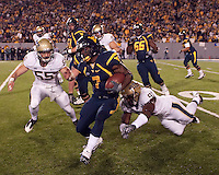 WVU running back Noel Devine (7) escapes the tackle of Pitt's Greg Romeus as Pitt linebacker Max Gruder (55) closes in. The West Virginia Mountaineers defeated the Pittsburgh  Panthers 19-16 on November27, 2009 at Mountaineer Field at Milan Puskar Stadium, Morgantown, West Virginia.