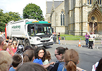 July 21, 2012: Crew member of a passing by vehicle pretends to carry Olympic Torch on Church Street in the town of Stoke Newington, London, England.