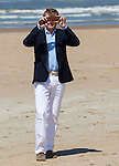 King Willem-Alexander of the Netherlands takes a photo of the photographers during a photo session on the beach near Wassenaar, the Netherlands, July 10, 2015. © Michael Kooren
