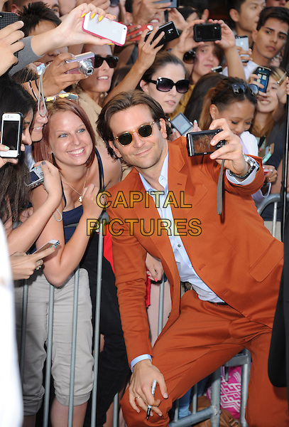 """Bradley Cooper.""""The Hangover Part III"""" Los Angeles Premiere held at the Westwood Village Theater, Los Angeles, California, USA..May 20th, 2013.half length sunglasses shades mobile camera fans crowd posing orange suit blue shirt taking picture photographs                                                 .CAP/DVS.©DVS/Capital Pictures"""