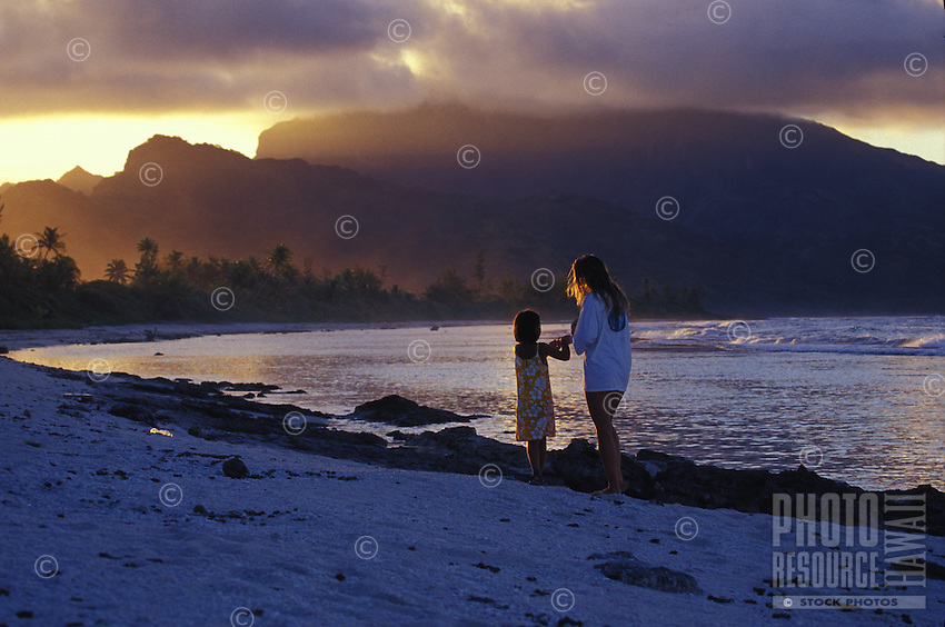 Mother and daughter collecting shells on beach at sunset, Huahine, Society Islands, French Polynesia