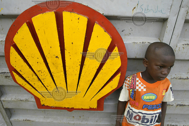 A young boy stands beside a large Shell sign in Warri, Nigeria's second largest oil town.