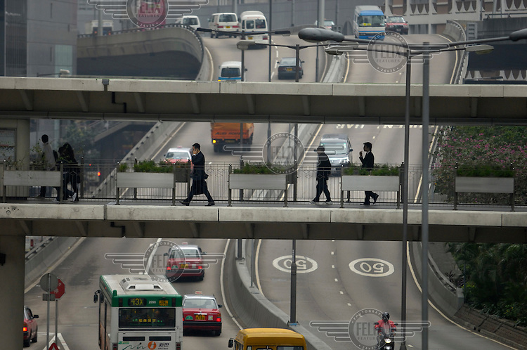 Businessmen using mobile phones while crossing traffic on an overpass in the Central District.