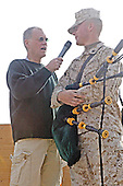 """David Letterman chats with Corporal Wesley McNallie with Marine Wing Support Squadron 373, who wowed the audience with his bagpipe performance, which included The Marines' Hymn, durng """"The Late Show"""" at Camp Taqaddum, Iraq, December 24, 2004. Letterman, along with his musical director Paul Shaffer and stage manager Biff Henderson, brought the popular late night television show to the Marines, sailors and soldiers currently stationed at Camp Taqaddum, Iraq. They were followed with a performance from """"Off the Wall,"""" a southern California band, which added to the holiday festivities..Mandatory Credit: Luis R. Agostini / USMC via CNP"""
