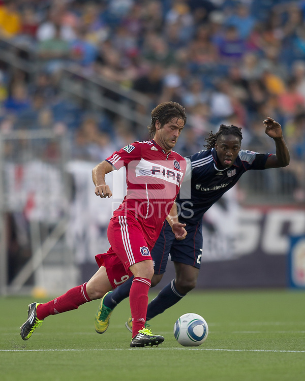 Chicago Fire forward Diego Chaves (99) dribbles as New England Revolution midfielder Shalrie Joseph (21) defends. In a Major League Soccer (MLS) match, the New England Revolution tied the Chicago Fire, 1-1, at Gillette Stadium on June 18, 2011.