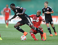 Washington D.C. - July 30, 2014:  Eddie Johnson (7) of D.C. United gets fouled by Collen Warner (26) of Toronto FC. D.C. United defeated the Toronto FC 3-1 during a Major League Soccer match for the 2014 season at RFK Stadium.