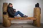 © Joel Goodman - 07973 332324 . 2 November 2013 . Chorlton Precinct (aka The Square ) Manchester , UK . Friend of Harry and Bee-Gee relation , HAZEL GIBB , sits on the bench with her camera . A bench in memory of photographer Harry Goodwin is unveiled at Chorlton Precinct . The locally created carved wood design features two cameras , one a historic twin-lens reflex design and the other a modern 35mm design . Photo credit : Joel Goodman