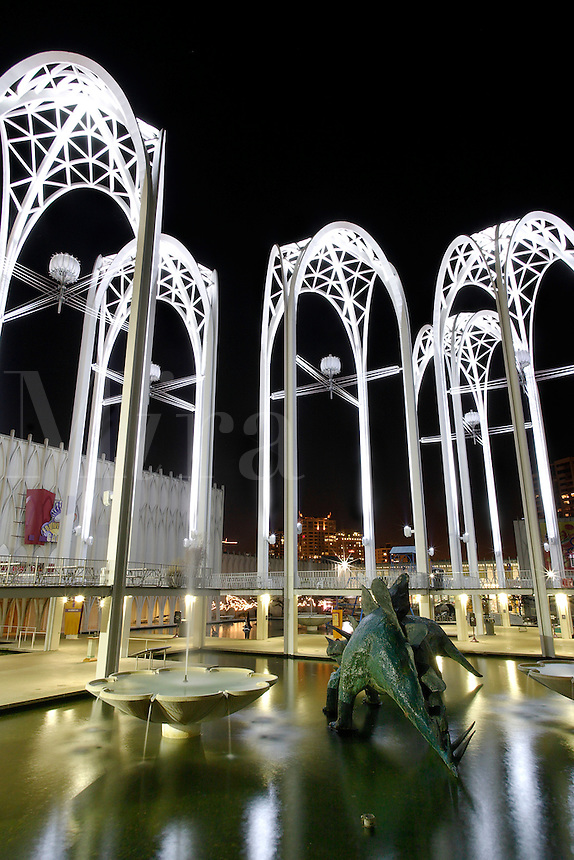 Nighttime scene of dinasour statues wading in pools at Pacific Science Center, Seattle Center, Seattle, Washington, US