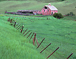 Wallowa County, OR<br /> Weathered barn (dated 1915) and meandering fence in a green valley of the Zumwalt praire
