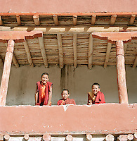 Novice child monks on balcony at monastery, Ladakh, India