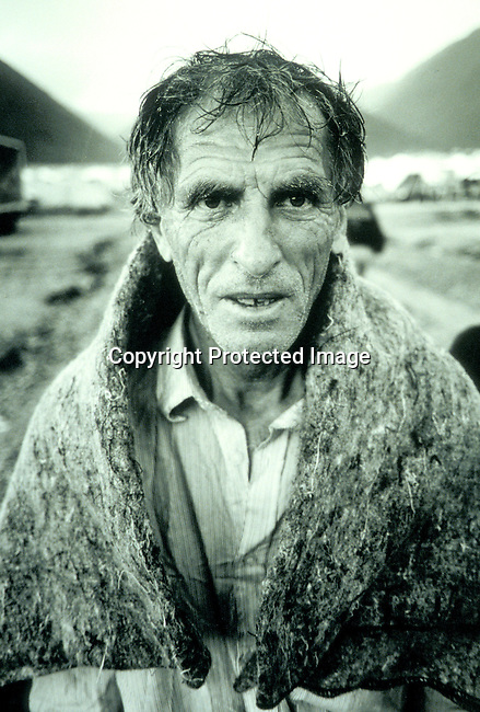 Un unidentified Kosovar refugee on April 25, 1999 using  a blanket to cover himself from a heavy rainfall in Cegrane, Macedonia. Hundreds of thousands of people fled Kosovo into Macedonia and Albania in the spring of 1999 due to Serb attacks on the minority group; refugees..©Per-Anders Pettersson/iAfrika Photos