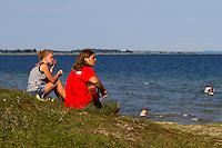 Kuba (Poland) playing guitar at the beach with Anna (Poland).  Photo: Mikko Roininen / Scouterna
