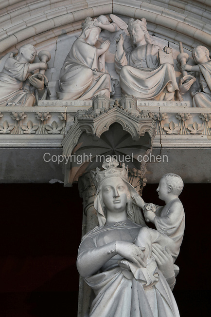 Low angle view of the statue of Virgin and Child decorating the trumeau of the portal to the lower chapel of La Sainte-Chapelle (The Holy Chapel), 1248, Paris, France. The tympanum depicting the coronation of the Virgin is visible above. La Sainte-Chapelle was commissioned by King Louis IX of France to house his collection of Passion Relics, including the Crown of Thorns. It is considered among the highest achievements of the Rayonnant period of Gothic architecture. Picture by Manuel Cohen