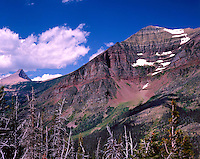 "Rising 4,450' above Two Medicine Lake, the red rock of Rising Wolf Mountain stands in contrast with the brilliant blue skies about Glacier National Park.  ""Mahkuyi-opuahsin"" and the surrounding region is sacred ground to the Blackfeet tribe."
