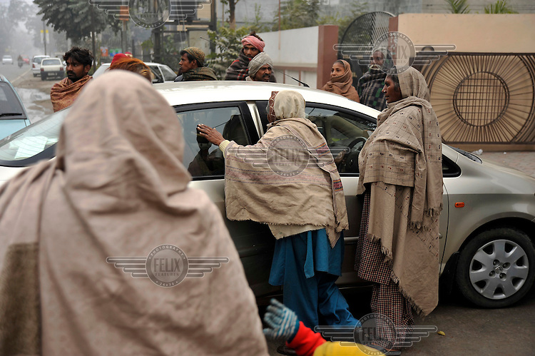 Beggars surround a car as it leaves the wedding ceremony of British/Punjabi couple Lindsay and Navneet Singh at a gurdwara in Amritsar.