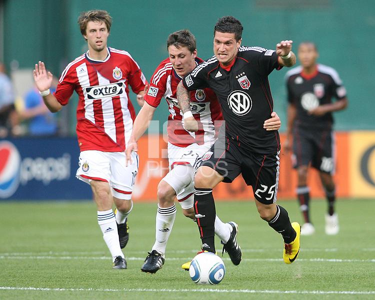Santino Quaranta #25 of D.C. United tries to break free from Ben Zemanski #21 of Chivas USA during an MLS match at RFK Stadium, on May 29 2010 in Washington DC. United won 3-2.