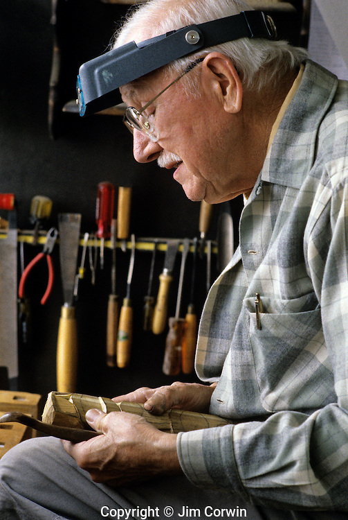 Wood carver in shop with tools sitting working on a piece of wood