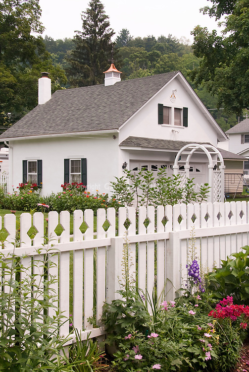 Classic white picket fence, flower garden, white house, flowers, perennials, windowboxes, in summer bloom