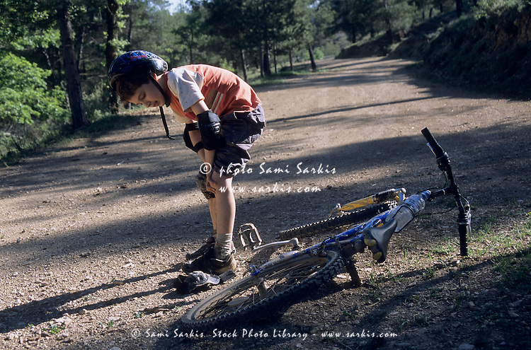 Boy rubbing his knee after falling off his bike, Vitrolles-en-Luberon, Provence, France.