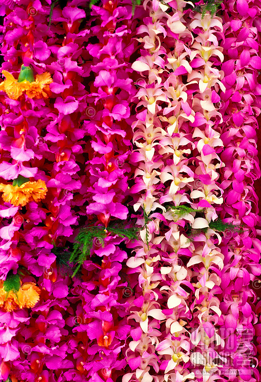 Dendrobium and vanda orchid leis, with a few carnations, for sale at an outdoor display during a high school graduation