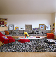 The black and white patterned sofa and shag-pile rug are offset by a bright red Saarinen Womb chair in this living room