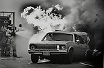 A vehicle erupts in flames as firefighters battle the blaze after a rear end collision along I-95 in Miami, circa 1980s.