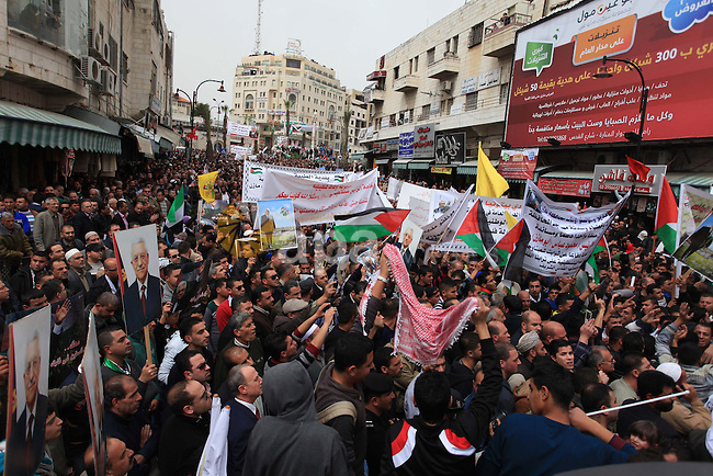 Supporters of the Palestinian president Mahmud Abbas hold his pictures during a support rally in the West Bank town of Ramallah, 17 March 2014, ahead of Abbas meeting with the US President Barack Obama in Washington, to advance the peace process between Israelis and Palestinians. Photo by Issam Rimawi