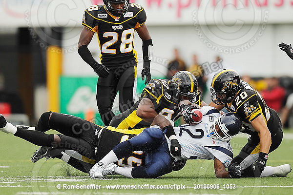 September 6, 2010; Hamilton, ON, CAN; Hamilton Tiger-Cats linebacker Otis Floyd (35), defensive tackle Demonte' Bolden (90) and defensive back Dylan Barker (20) tackle Toronto Argonauts running back/slotback Andre Durie (32). CFL football: Labour Day Classic - Toronto Argonauts vs. Hamilton Tiger-Cats at Ivor Wynne Stadium. The Tiger-Cats defeated the Argonauts 28-13. Mandatory Credit: Ron Scheffler.