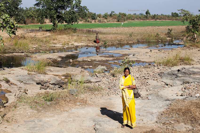 Shanti Adivasi, 52, a community journalist since 2002 at Khabar Lahariya newspaper poses for a portrait at a dried up river in Manikpur, Chitrakoot, Uttar Pradesh, India on 6th December 2012.  She has played a pivotal role in campaigning for water to be supplied to arid villages in the desert-like hills of Manikpur. Shanti used to be a wood gatherer, working with her parents since she was 3, and later carrying up to 100 kg of wood walking 12km from the dry jungle hills to her home to repack the wood which sold for 3 rupees per kg. After learning to read and write in an 8 month welfare course, at age 32, she became a reporter, joining Khabar Lahariya newspaper since its establishment in 2002, and making about 9000 rupees per month, supporting her family of 14 as the sole breadwinner. Photo by Suzanne Lee for Marie Claire France.