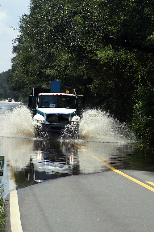 A county truck plows through the flooding from Lake Lafayette as it drives down Chaires Cross Road.