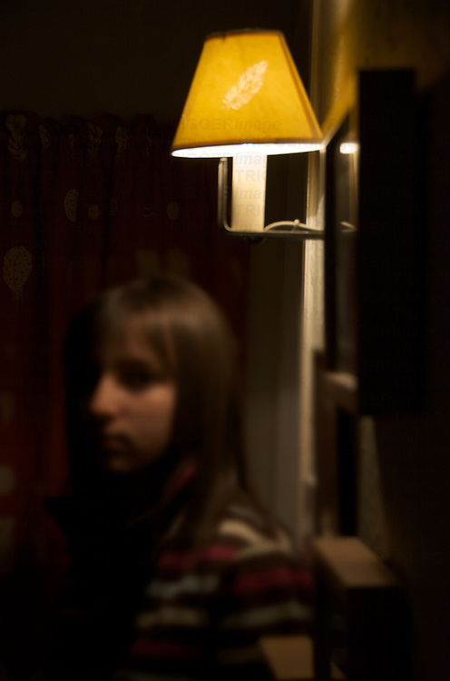 A young girl standing alone in a room under a wall light looking at camera