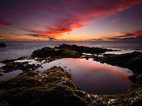 Bright red clouds fill the sky and are reflected in a tidal pool at Keahole Point, Kailua-Kona, Big Island.