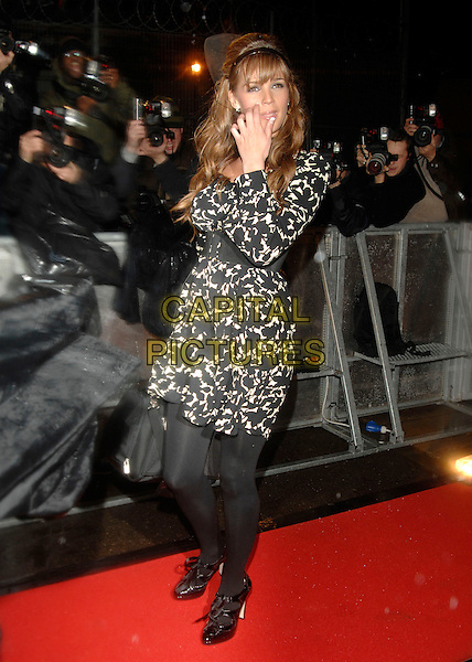 DANIELLE LLOYD.Celebrity Big Brother arrivals at the House..Borehamwood, Hertfordshire, England.3rd January 2007.full length black white dress belt pattern bag hand on face.CAP/PL.©Phil Loftus/Capital Pictures.