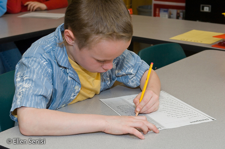 MR / Schenectady, NY.Yates Arts-in-Education Magnet School (urban public elementary school).Self-Contained Special Education Class - but students also mainstreamed several hours a day..Boy (9) working on reading worksheet..MR: Gle2.© Ellen B. Senisi