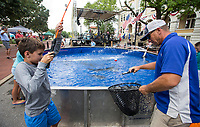 NWA Democrat-Gazette/BEN GOFF @NWABENGOFF<br /> Campbell Laws, 10, of Rogers reels in a catfish with help from JP Brazeal of the Kid Fish Foundation based in Little River, Texas, Friday, July 5, 2019, during First Friday on the Bentonville Square. The theme for July was 'Great Outdoors.' Kid Fish brought their tank stocked with catfish to the square in partnership with Nunnally Chevrolet. They have set up the tank at the Bentonville dealership in the past.