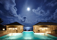 Two private villas, lit at night, are set either side of an infinity pool and look out over the sea beyond.