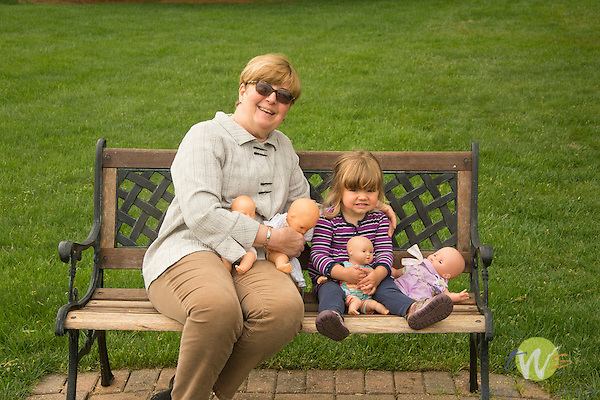 Grandmother and granddaughter on park bench with four doll babies.
