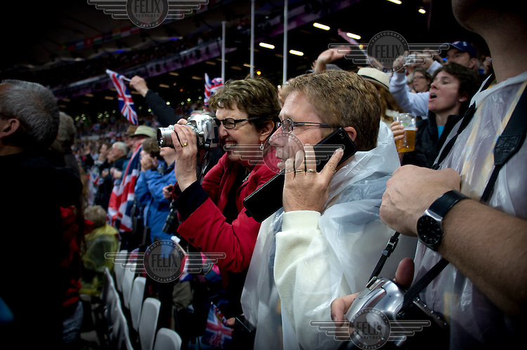 A spectator takes a photograph while her companion makes a call on a mobile phone during the Olympic 1500 metres athletics final at the Olympic Stadium in Stratford, East London.