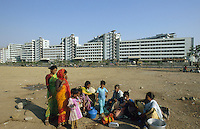 INDIA, Mumbai, Bandra-Kurla-complex, homeless family with radio in front of new business building / INDIEN Bombay, obdachlose Familie mit Radio vor Neubau eines Geschaeftshauses in der Megacity