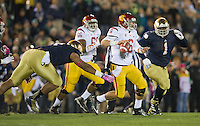 Trojans quarterback Cody Kessler (6) is pressured by Notre Dame Fighting Irish defensive end Stephon Tuitt (7) and nose tackle Louis Nix (1).