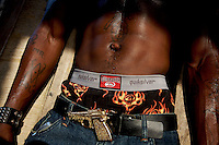 Nimley, 26 years old, shows his muscles while lifting weights in his neighborhood improvised gym in Monrovia, Liberia on Tuesday  March 20 2007. .Marshall, Nimley and the other men working out are all unemployed. they spend their days at the gym to fight chronic depression..