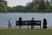 Two women sitting on a park bench, Kensington Gardens, London.