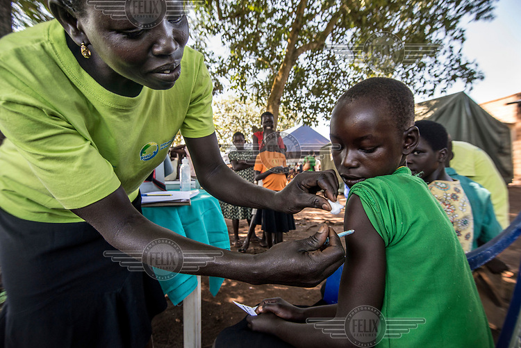 An RHU (Reproductive Health Uganda) staff member administers a vaccine during a mobile clinic visit to the village of Ochaga, near Gulu.