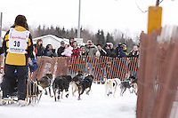 Saturday March 6 , 2010   A crowd of spectators along the trail during the ceremonial start of the 2010 Iditarod in Anchorage , Alaska cheer on Michael Suprenant and team .