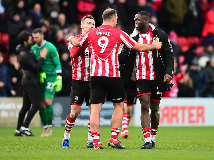 Lincoln City's Matt Rhead celebrate the victory with Harry Toffolo, left, and John Akinde, right<br /> <br /> Photographer Andrew Vaughan/CameraSport<br /> <br /> The EFL Sky Bet League Two - Lincoln City v Grimsby Town - Saturday 19 January 2019 - Sincil Bank - Lincoln<br /> <br /> World Copyright &copy; 2019 CameraSport. All rights reserved. 43 Linden Ave. Countesthorpe. Leicester. England. LE8 5PG - Tel: +44 (0) 116 277 4147 - admin@camerasport.com - www.camerasport.com