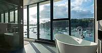 BNPS.co.uk (01202 558833)<br /> Pic: LillicrapChilcott/BNPS<br /> <br /> Bath views...<br /> <br /> A brand new futuristic property perched right on the edge of a sea wall overlooking some of the finest sailing waters in the country has gone up for sale for £4.5m.<br /> <br /> The ultra-modern home and just been built on remote headland in the Cornish sailing village of St Just.<br /> <br /> It replaced a large bungalow that stood on the coastal plot for over 80 years and was demolished by owner and architect Callum Wason.