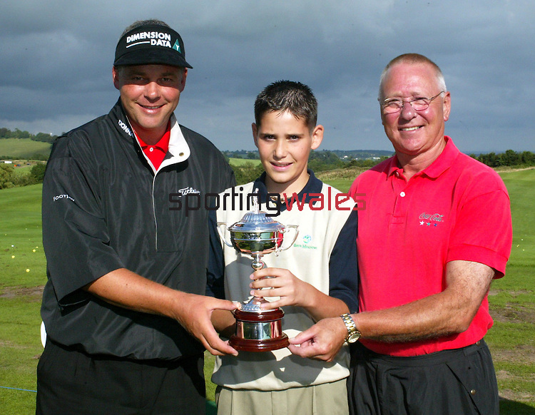 Darren Clark and Jim Pilgrim with Coca-Cola junior Wales Open winner 12 year-old Matteo Rossi from Llanbradach, Caerphilly.Wales Open 2002.The Celtic Manor Resort